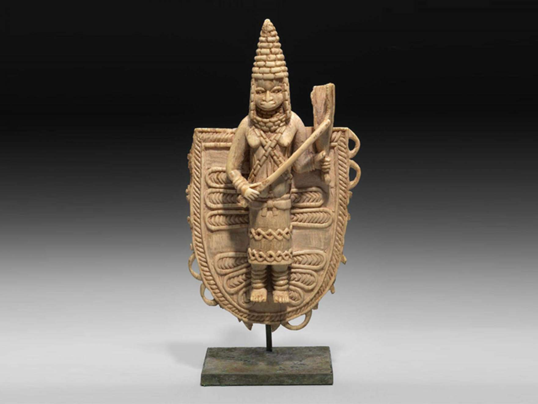 Ivory pendant of a queen in a headdress holding a baton