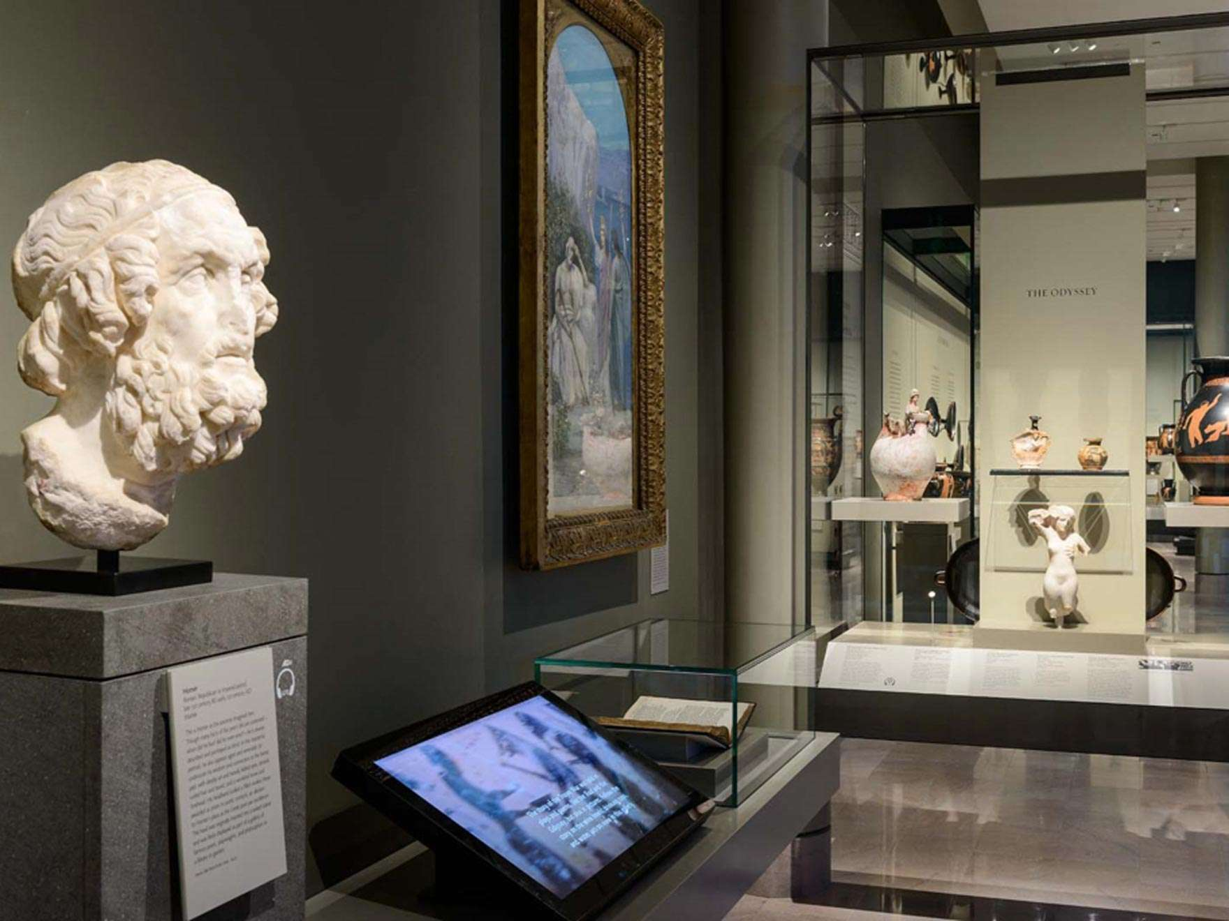 View of Greek gallery with bust in foreground next to interactive screen