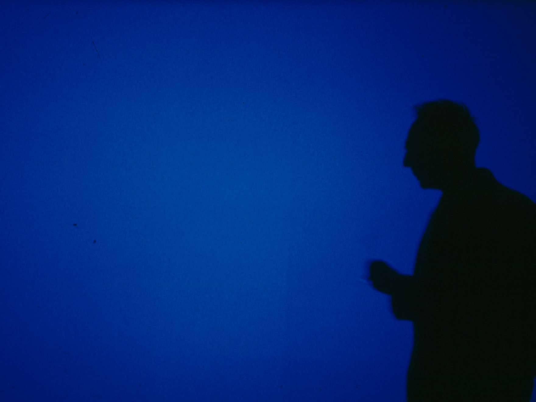 Silhouette of Derek Jarman in front of his projected film, Blue