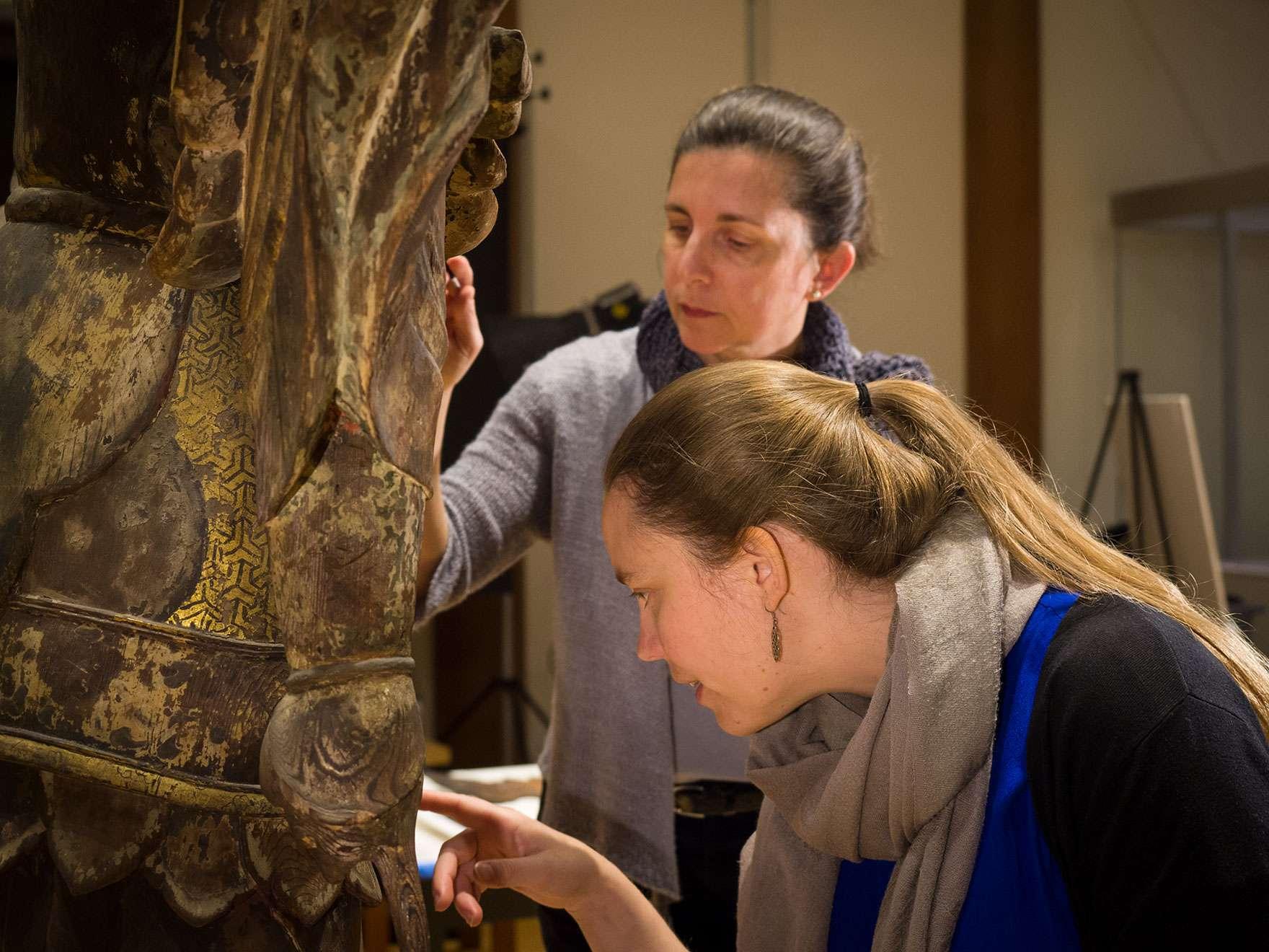 Conservators working on Japanese Buddha sculpture