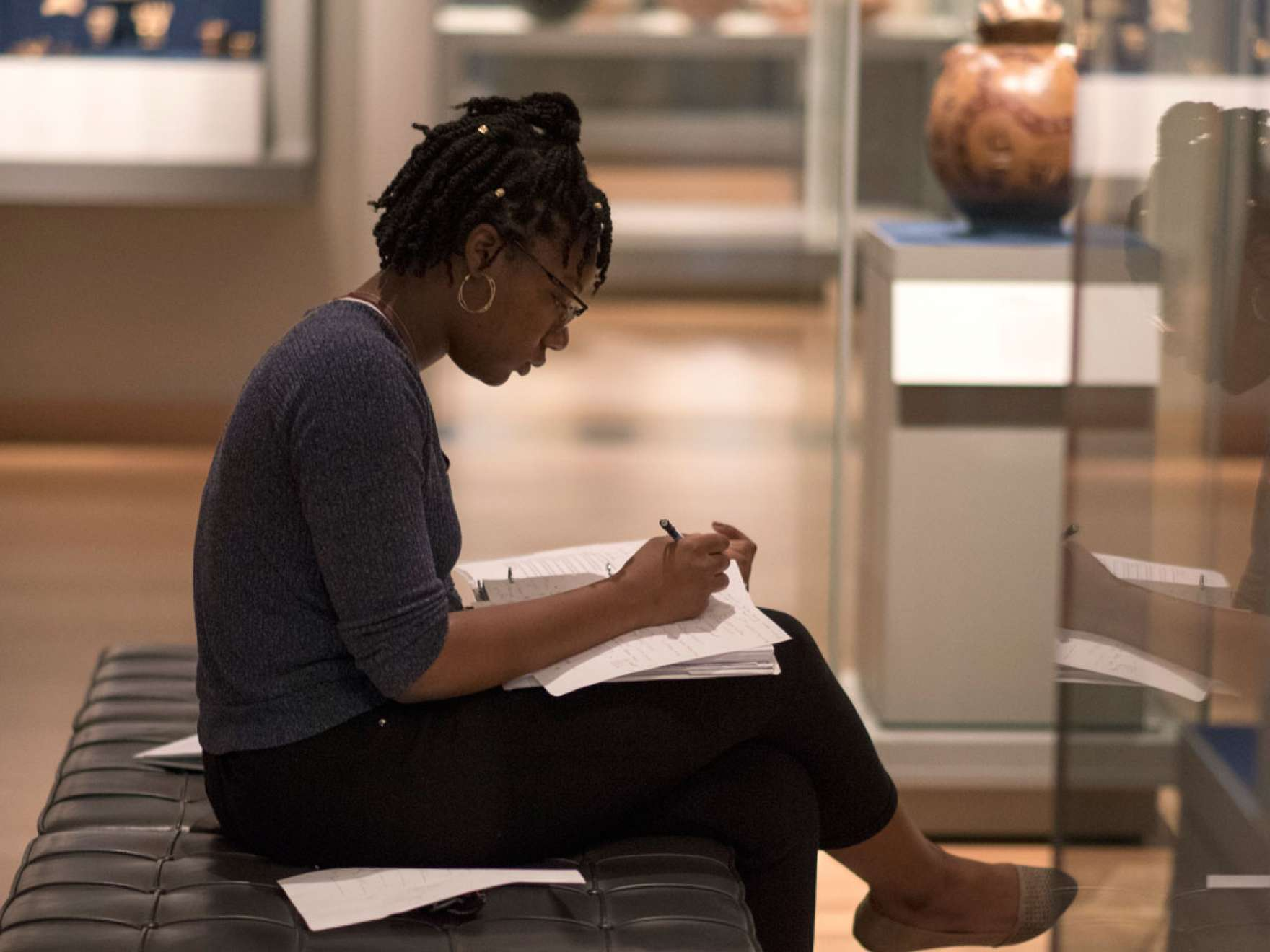 Visitor sitting on gallery bench writing in binder in front of Mayan display case