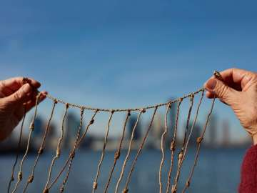 Photograph of Cecilia Vicuña's hands holding quipu during her 2006 performance work, Skyscraper Quipu in New York