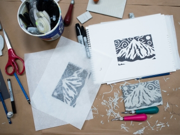 Top view of student's workstation including print block, sketches, tools and finished print of mountain scene