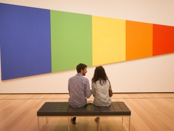 Two visitors sitting on gallery bench, looking at Ellsworth Kelly's Blue Green Yellow Orange Red