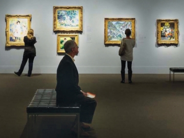 Visitor seated in Impressionist Gallery