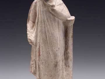 Figurine of a man leaning against a pillar
