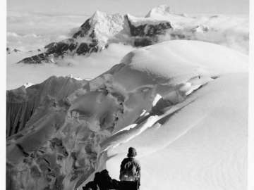 Barbara Washburn descending the first few steps below the summit of Mount Bertha, Alaska
