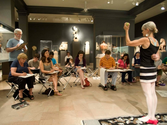 Visitors sitting on foldable chairs in Classical gallery sketching model holding green apple