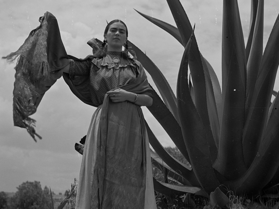 """Toni Frissell, Frida Kahlo (Senora Diego Rivera) standing next to an agave plant, during a photo shoot for Vogue magazine, """"Senoras of Mexico"""", 1937"""