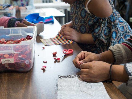 Close up of hands as girls choose buttons for sewing project