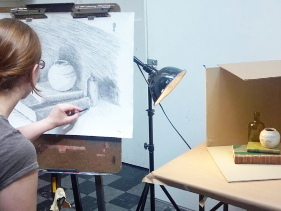 Student draws from still life in studio class