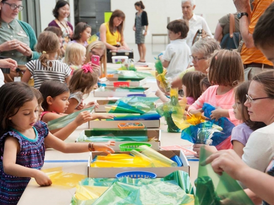 Children working on craft using colored cellophane at long table