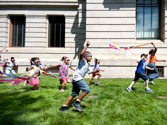 Kids in sunglasses running on Museum lawn, flying kites