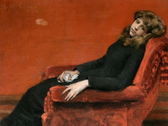 Woman with brown hair wearing long black dress laying back in a chair