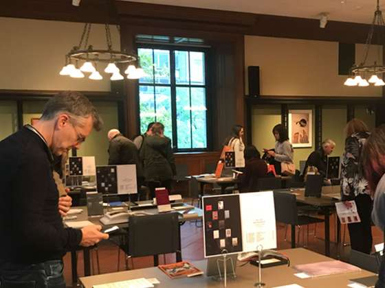 Attendees browsing photo books on tables for 10x10 Photobooks event