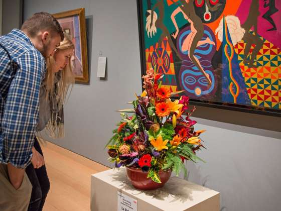 Two visitors crouch down to examine flower arrangement in front of Loïs Mailou Jones' La Baker painting
