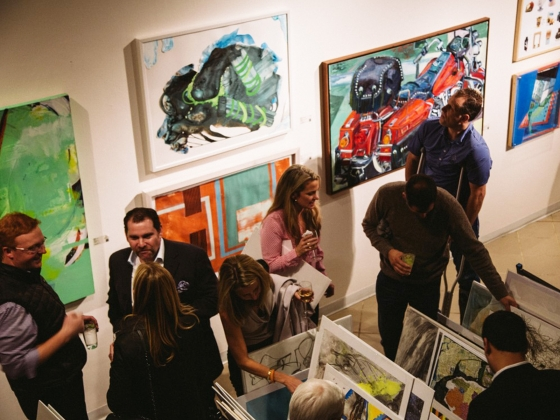 SMFA art sale attendees perusing prints in racks and looking at paintings on wall