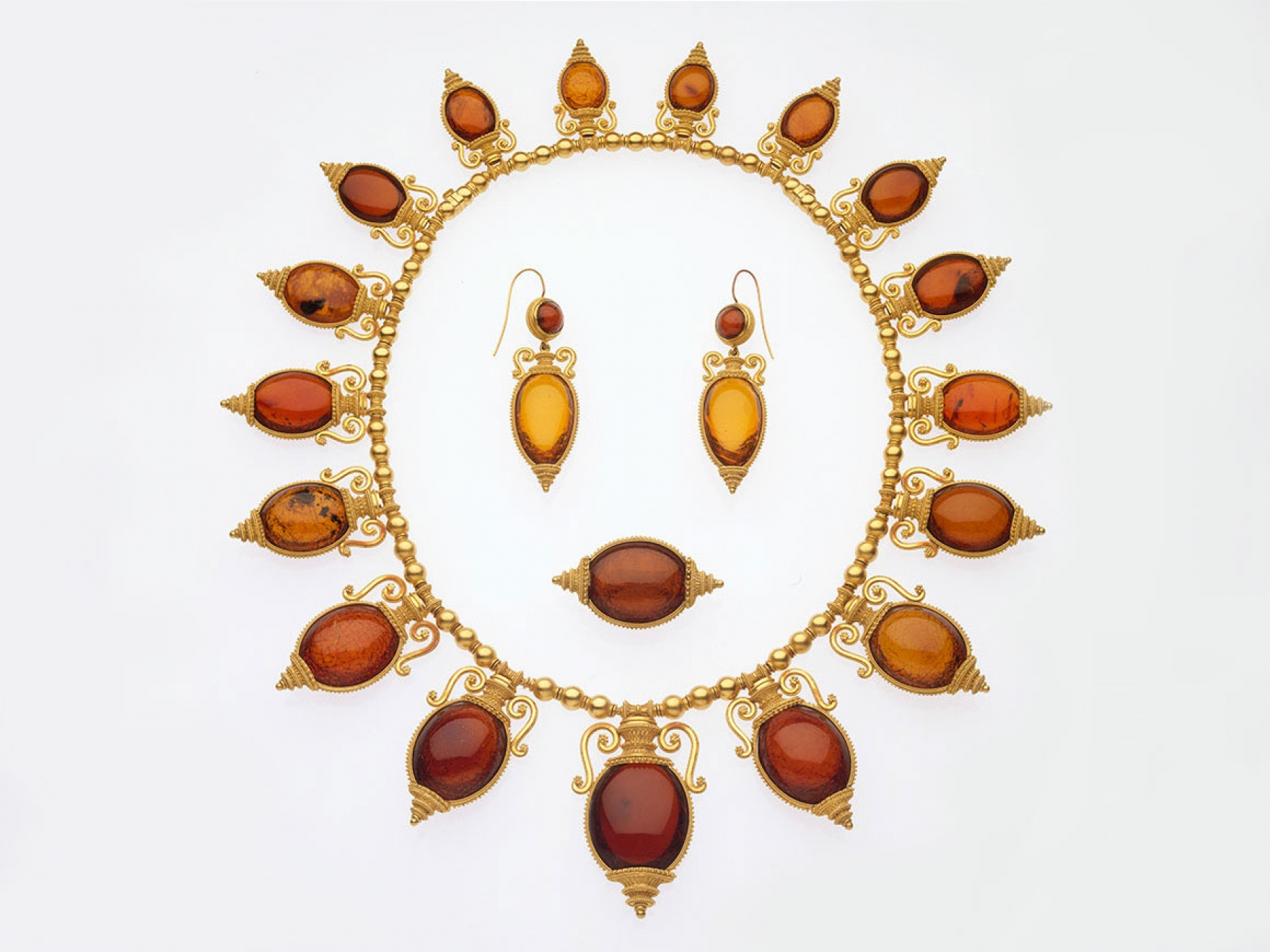 Necklace, brooch, and earrings in the archaeological revival style, possibly by Castellani, made of gold and amber.