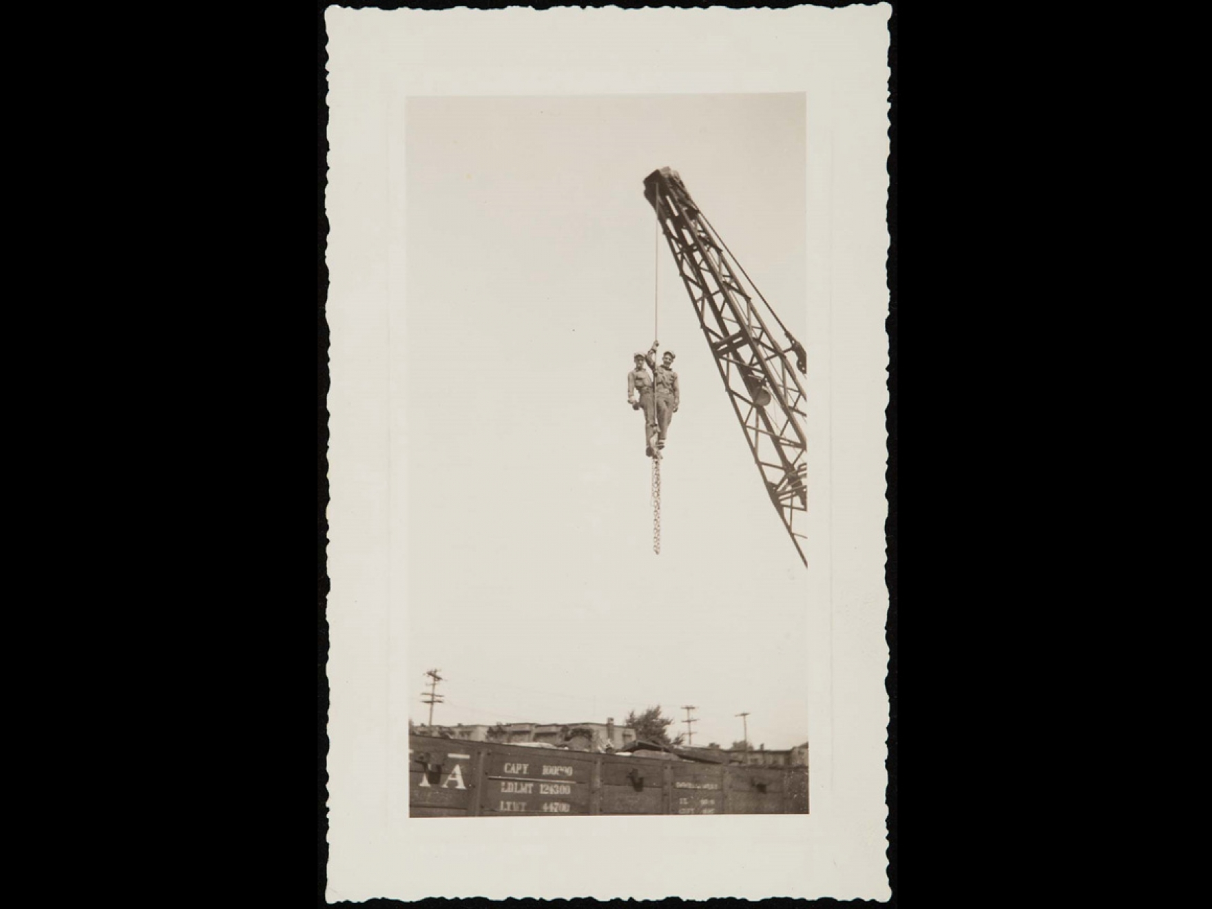 Two men hanging from a crane