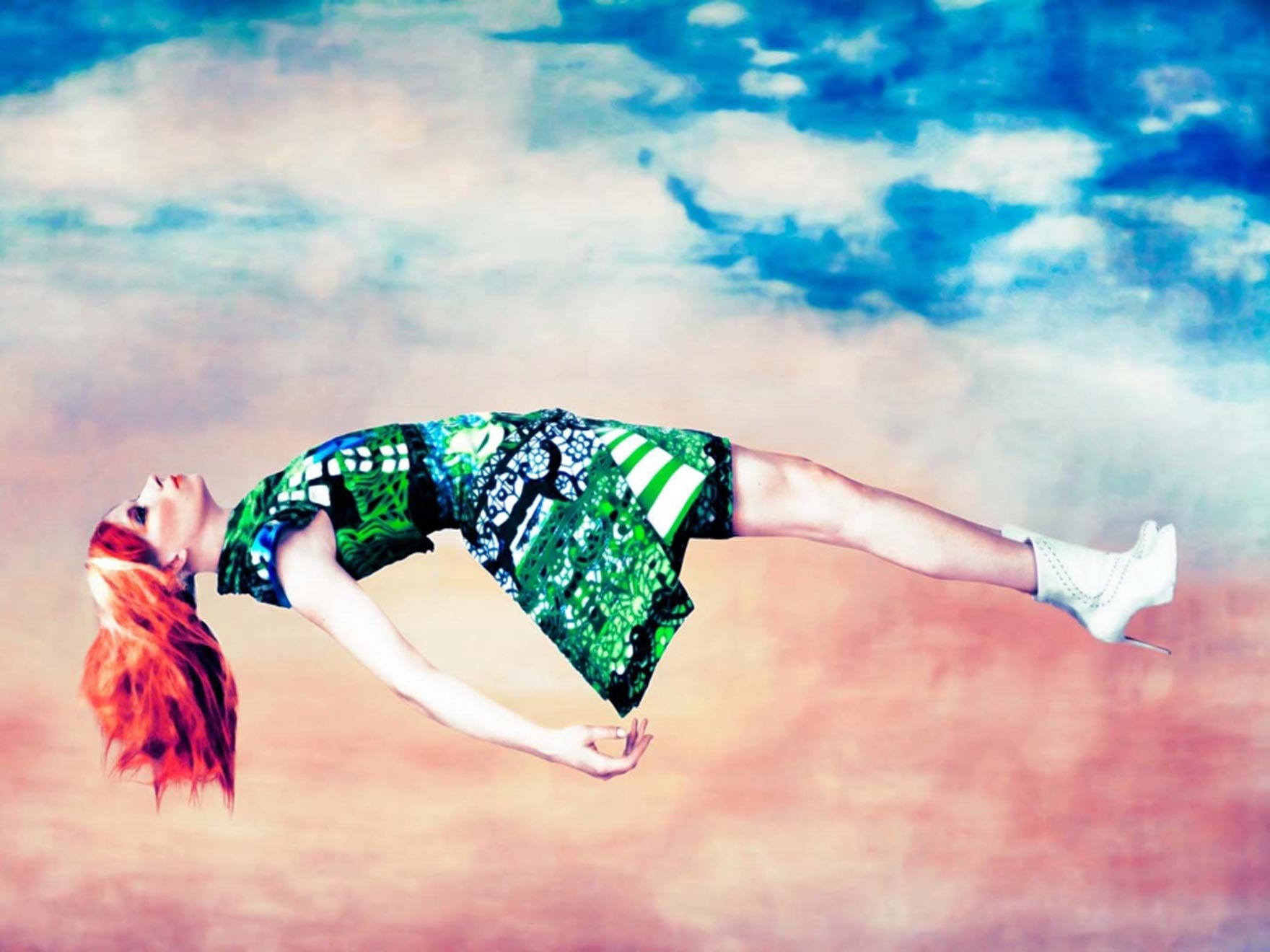Fashion model wearing green dress, floating in the clouds