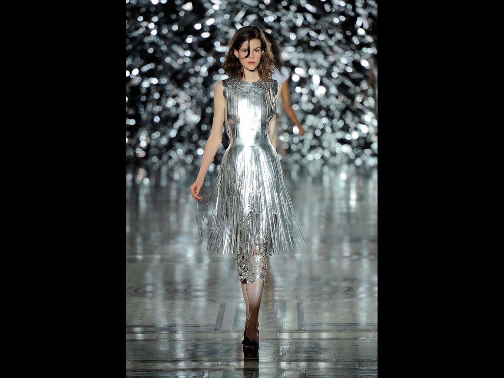 Fashion model wearing dress with silver sheen on runway