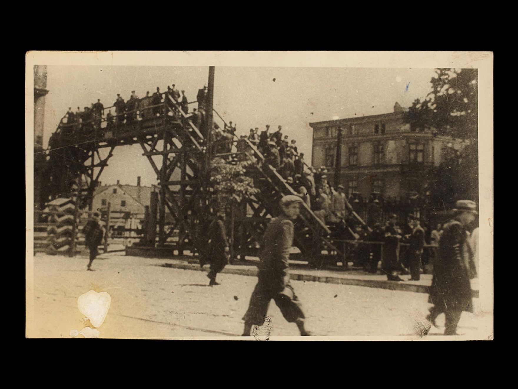 "Henryk Ross's photograph, Boy walking in front of the bridge crossing Zigerska (the ""Aryan""), 1940–42"
