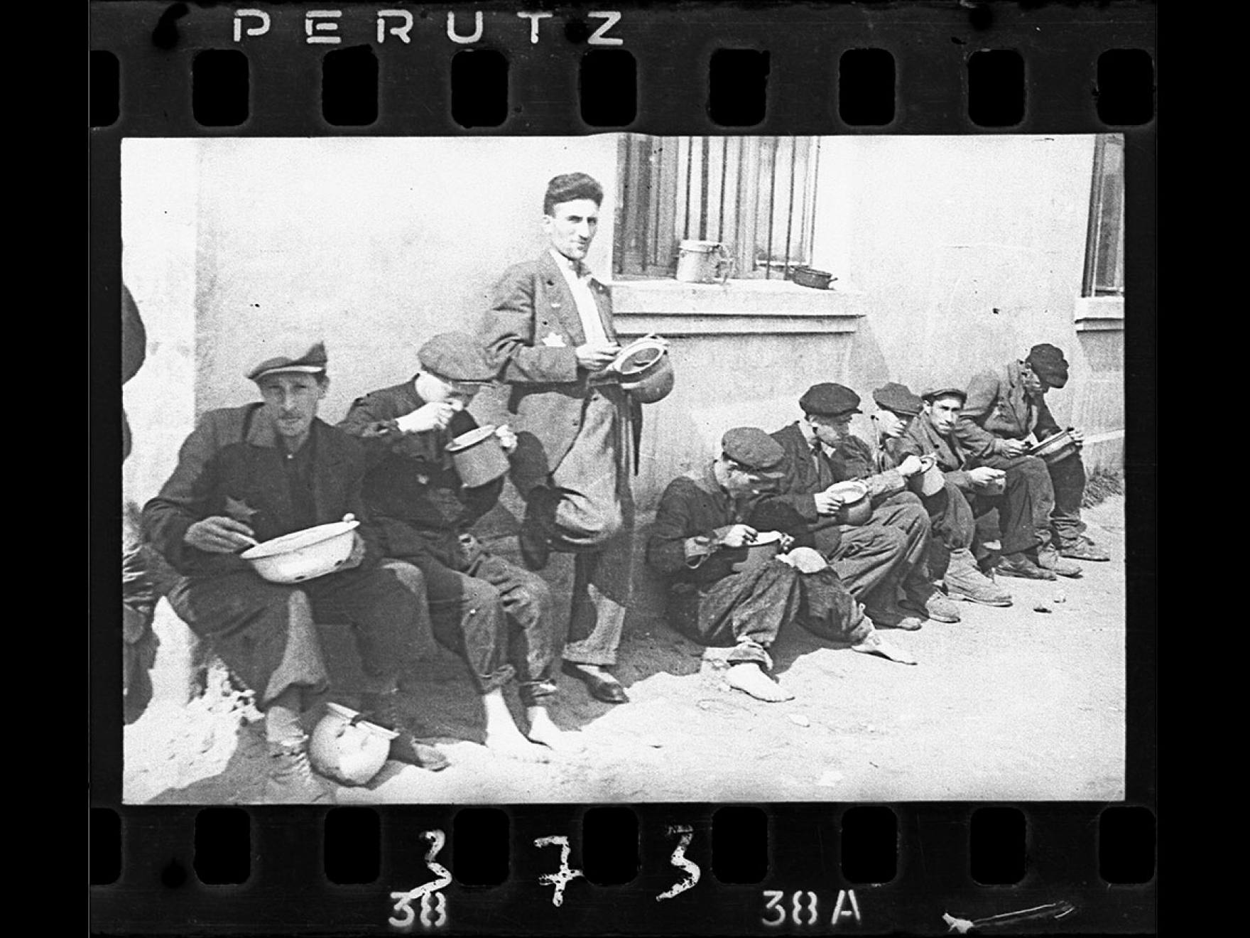 """Henryk Ross's photograph,""""Soup for lunch"""" (Group of men alongside building eating from pails), 1940–44."""