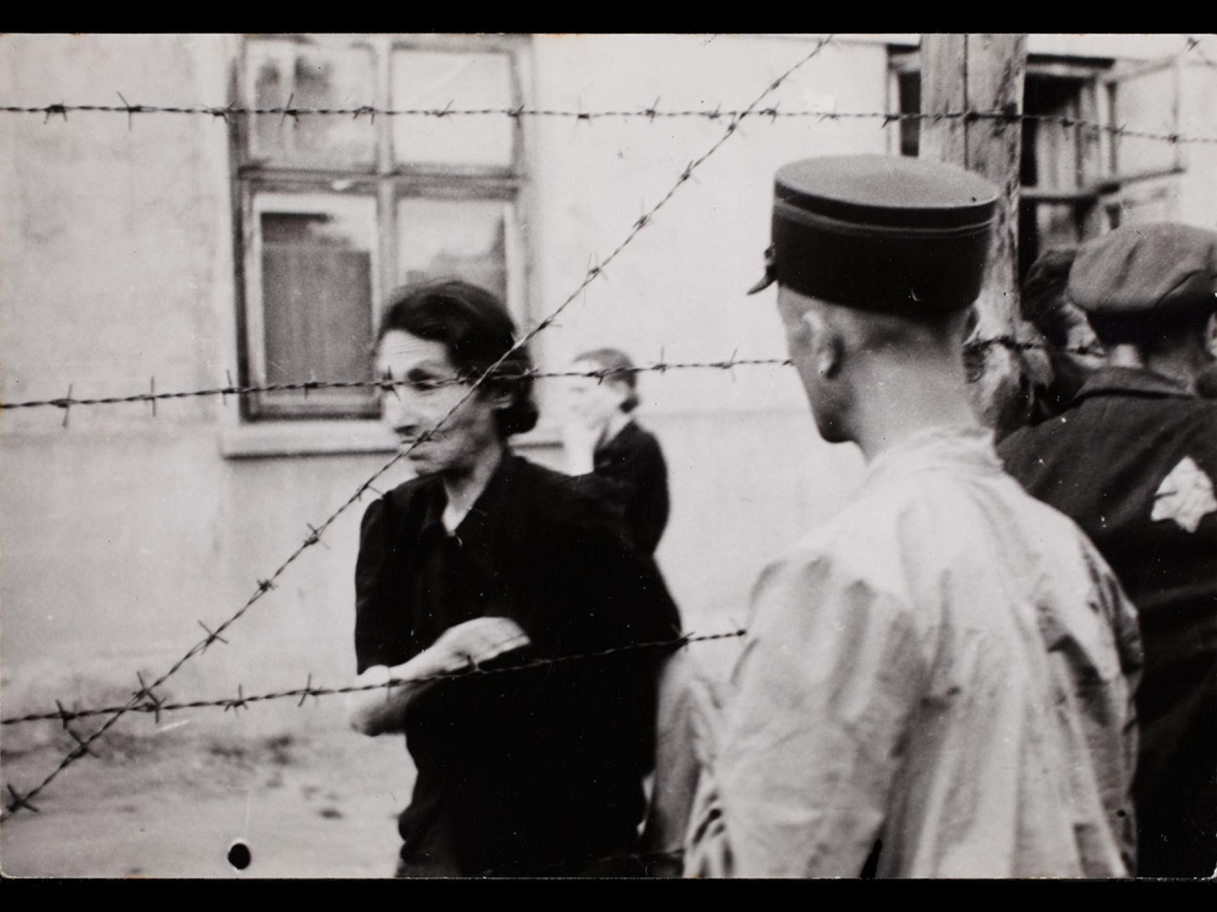 Henryk Ross's photograph, Ghetto police with woman behind barbed wire, 1942