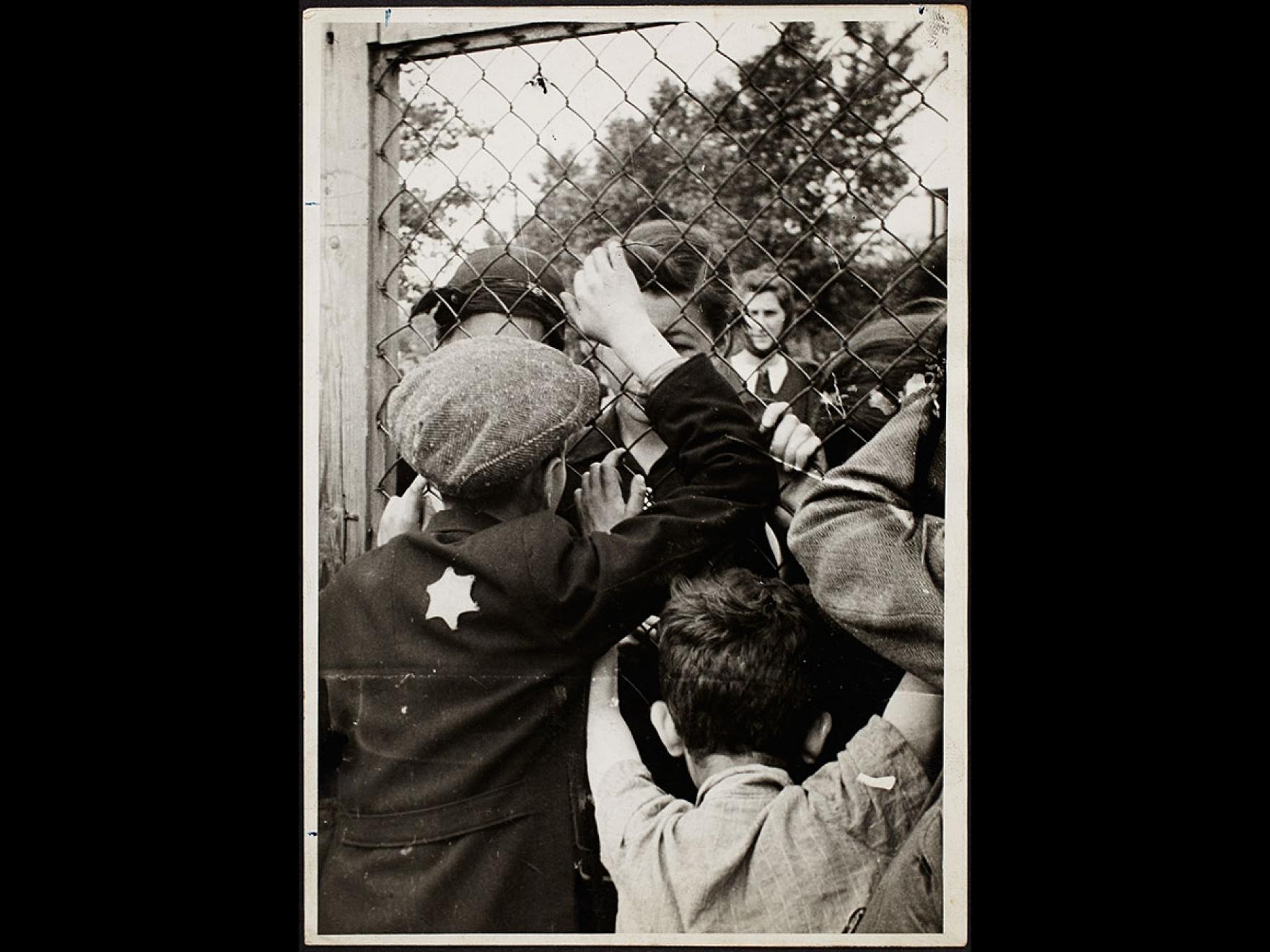 Henryk Ross's photograph, Children talking through fence of central prison on Czarnecki Street prior to deportation, 1940–42
